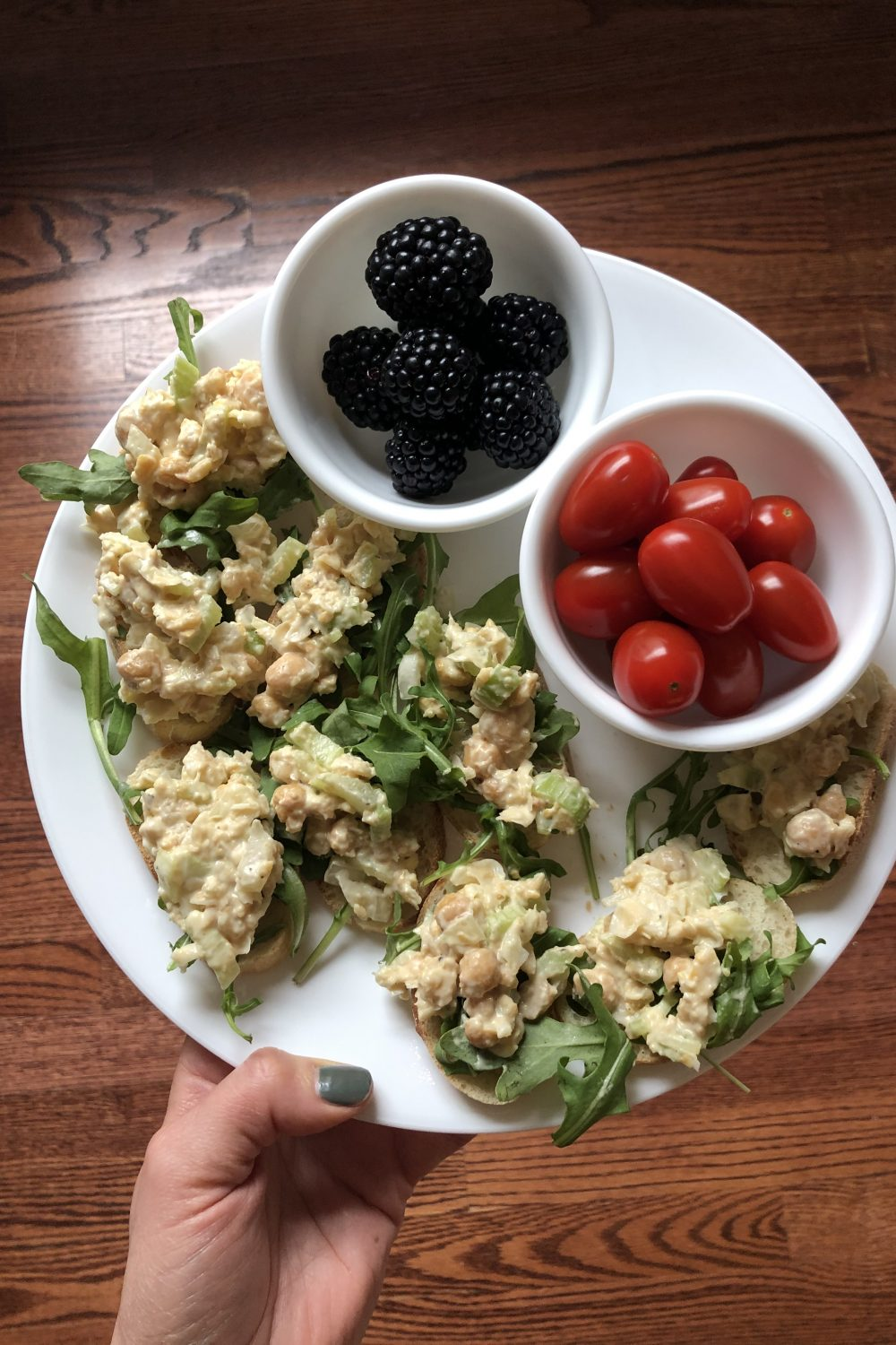 Chickpea salad and arugula on slices of baguette with a side of blackberries and a side of cherry tomatoes