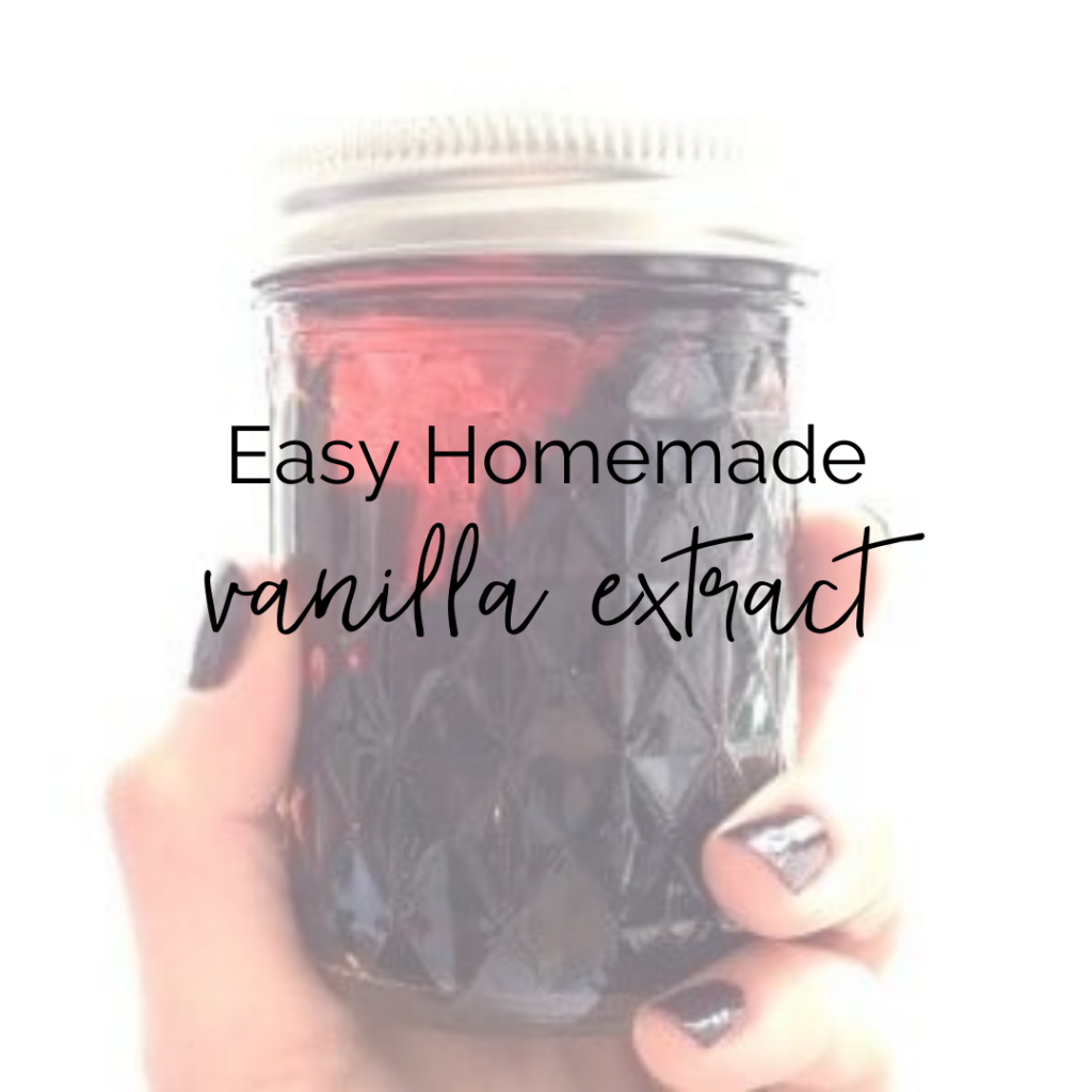 hand with painted nails holding a small jar of vanilla extract