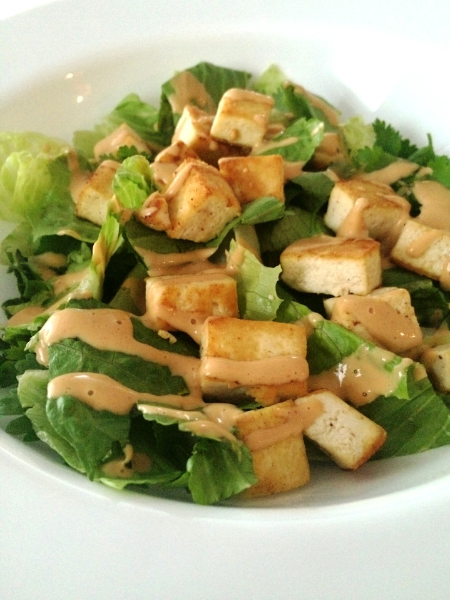 peanut sauce drizzled over a bed of greens and baked tofu