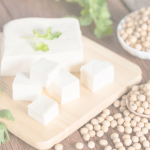 Cubed tofu on wooden board and soy beans