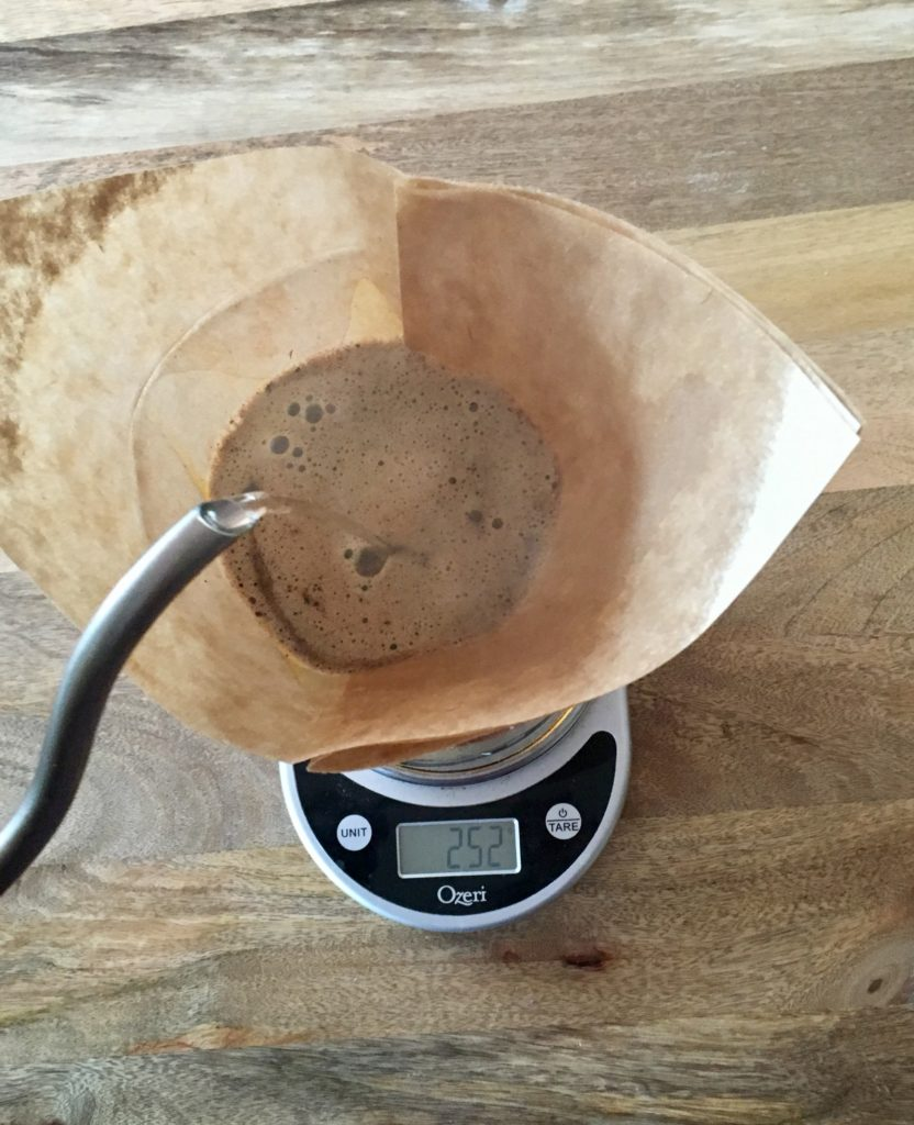 Hot water being poured into coffee in a filter in a Chemex sitting on a scale