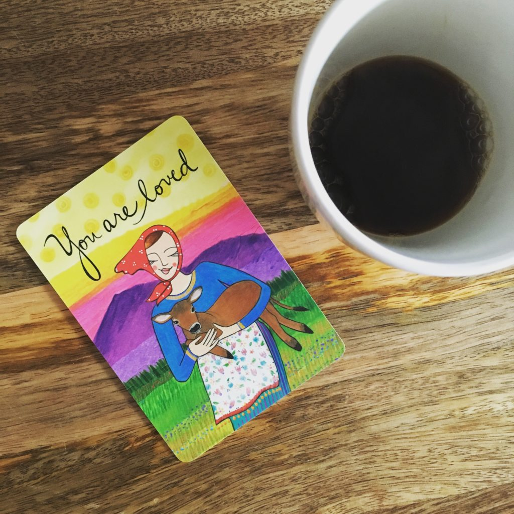 """A cup of coffee next to a card that says """"you a loved"""""""