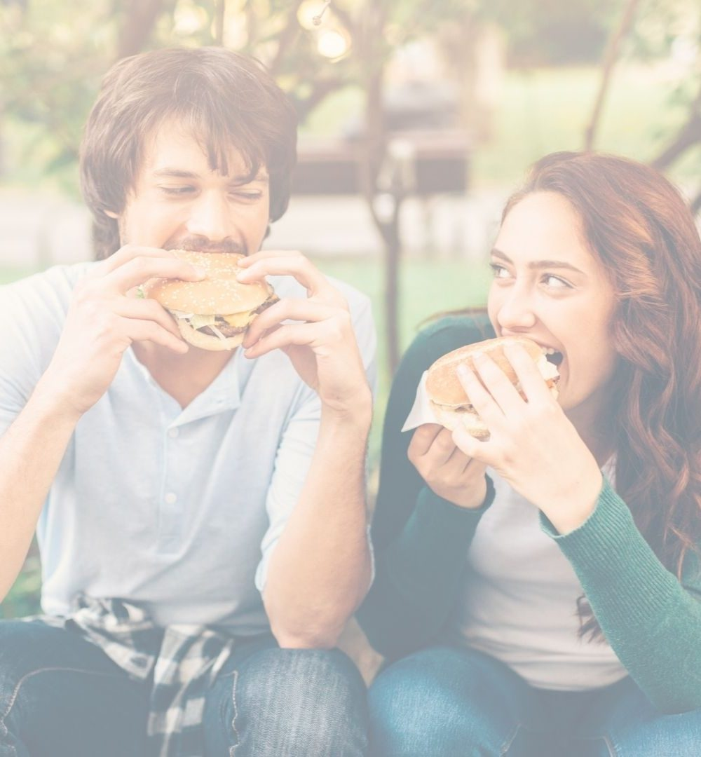 young man and woman sitting outside eating hamburgers and looking at each other with happy faces