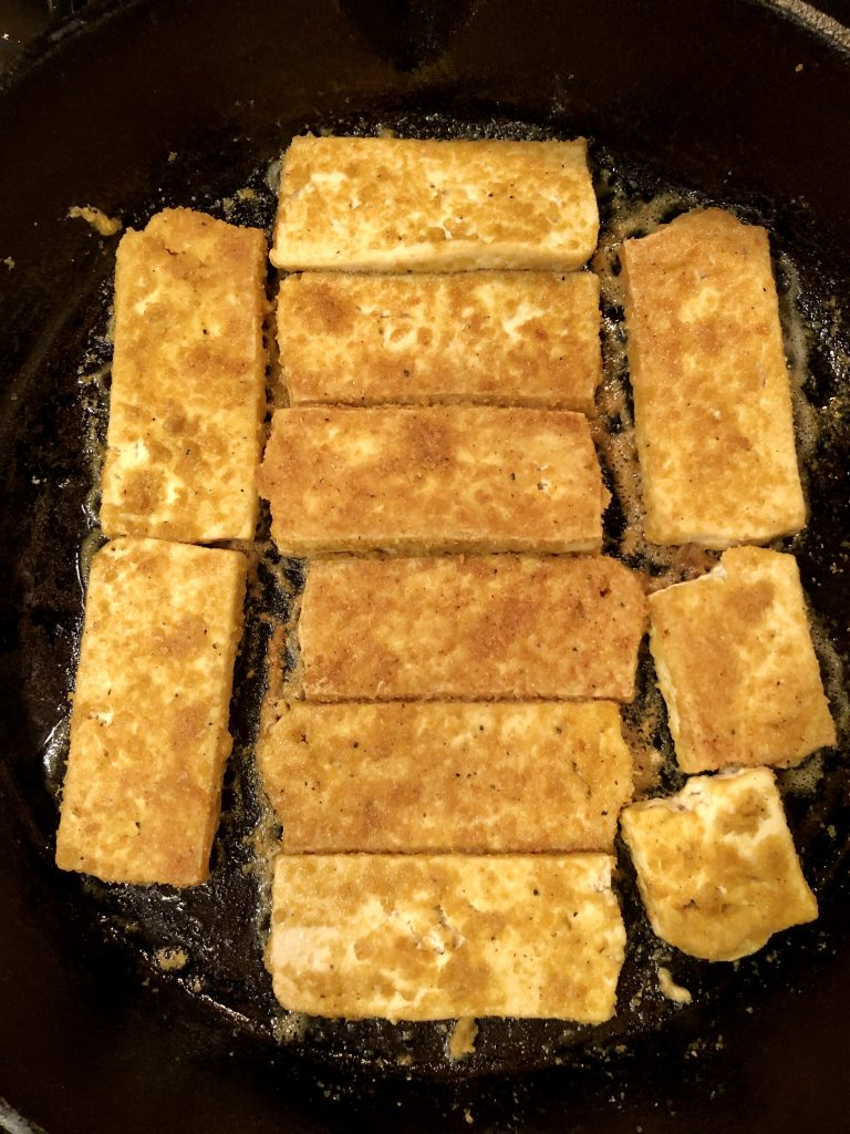 Nooch tofu cooking in pan