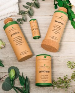 Bottles on wood background : Natural Vegan Club | Habitat Botanicals - 100% Vegan, Zero-Waste Hair and Body Care