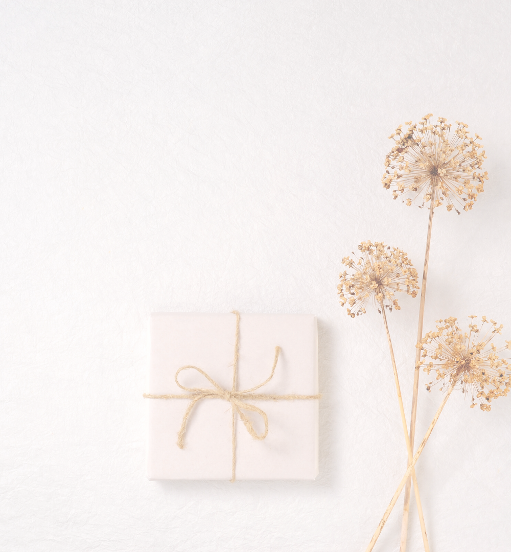 Small gift wrapped in paper, wrapped in twine. Sitting next to dried flowers.