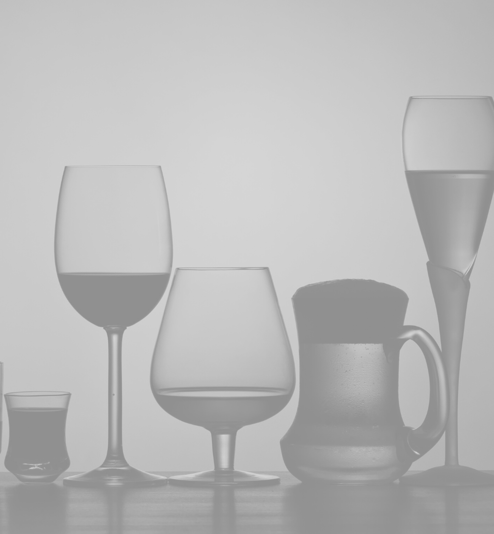 Greyscale image of various glasses of alcohol, including wine and beer.