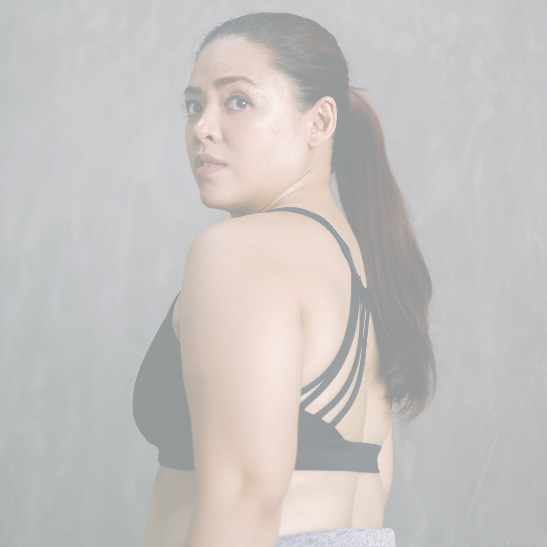 Image of a latinx woman in a sports bra looking over her shoulder with a serious expression on her face