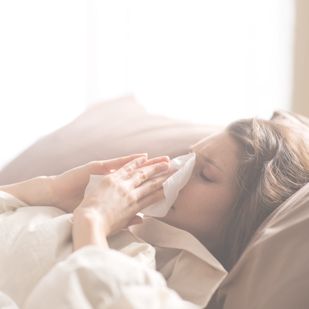 Woman lying down in bed blowing her nose, presumably with a cold