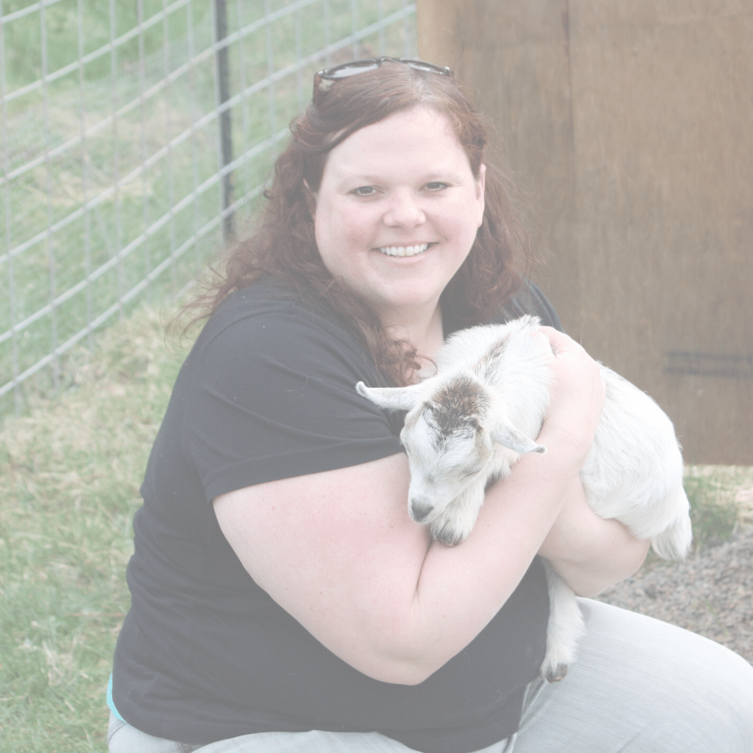 Chelsea Lincoln, a fat vegan activist smiling while holding a baby goat