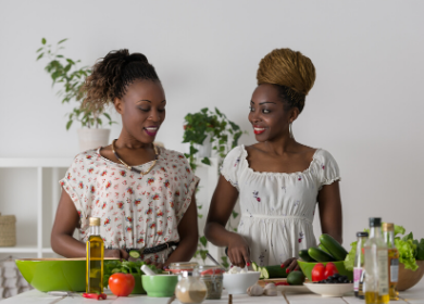 Two young black women making a salad together