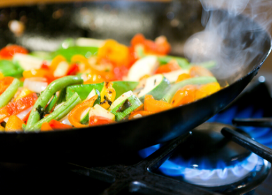 Close-up of a wok over a flame, filled with vegetables
