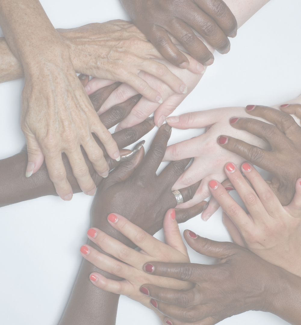 Black, brown and white hands overlapping and holding each other. Some hands have painted fingernails.