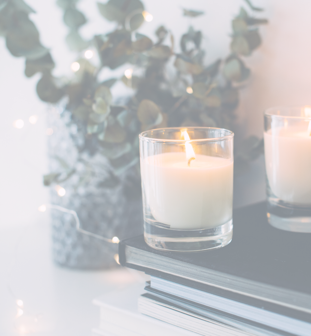 Stock image of a short stack of books with two lit candles on top, and a vase of dried eucalyptus in the background