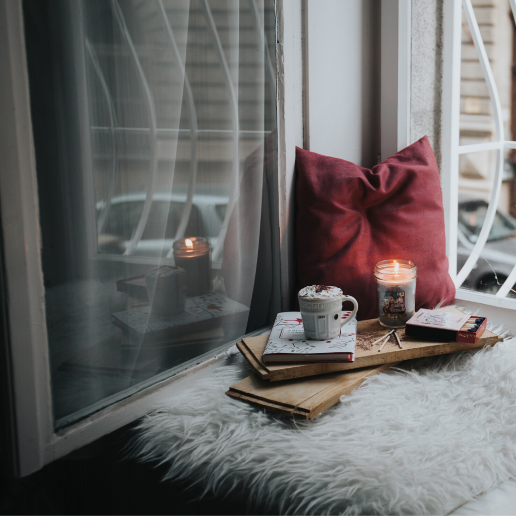 Stock image of a cozy scene near an open window with a fuzzy blanket, soft pillow, books, lit candle and frothy drink