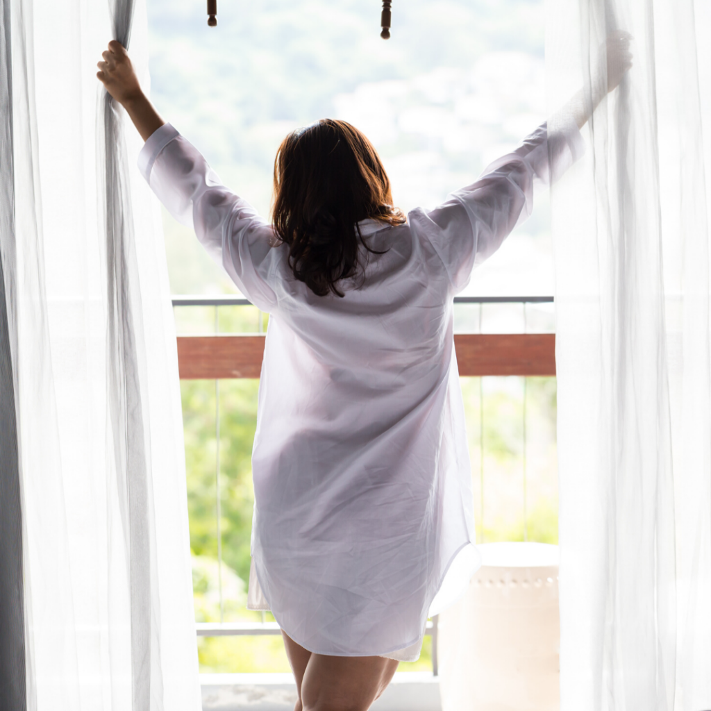Woman in pajamas opening curtains