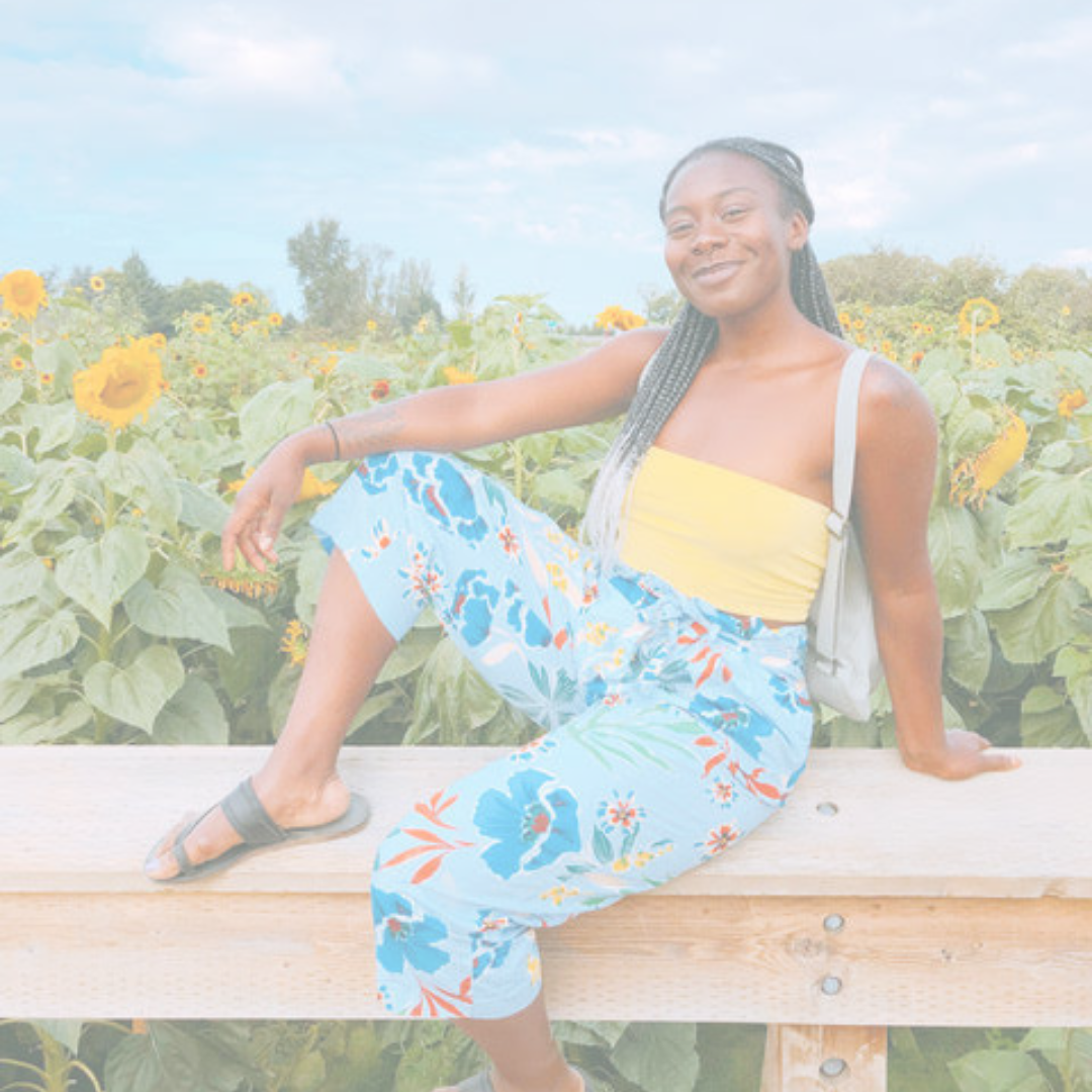 Zipporah sitting in front of a field of flowers