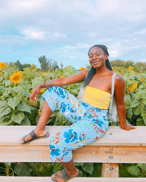 Zipporah the Vegan in front of a field of flowers