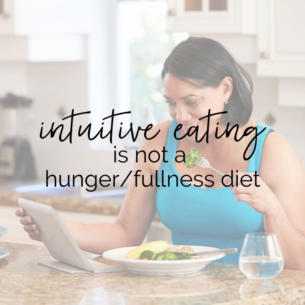 """Woman eating in her kitchen. Text overlay says """"intuitive eating is not a hunger/fullness diet"""""""